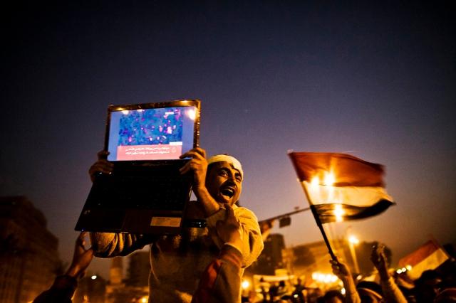 Un hombre en El Cairo alza una computadora portátil que muestra una imagen de las celebraciones en Egipto después de escuchar la noticia de que Mubarak había renunciado. (Guy Martin para el Wall Street Journal)